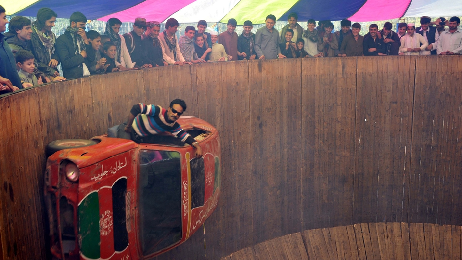 An Afghan circus performer drives a car on a 'Wall of Death' on the third day of Eid al-Adha in Jalalabad