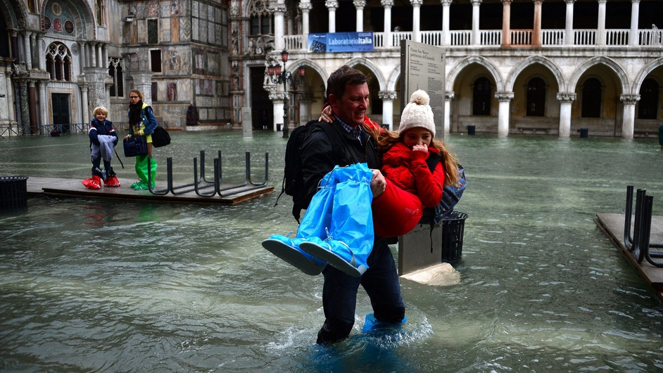 A man carries a girl as they leave the flooded St Mark's Square in Venice during 'acqua alta' (high water)