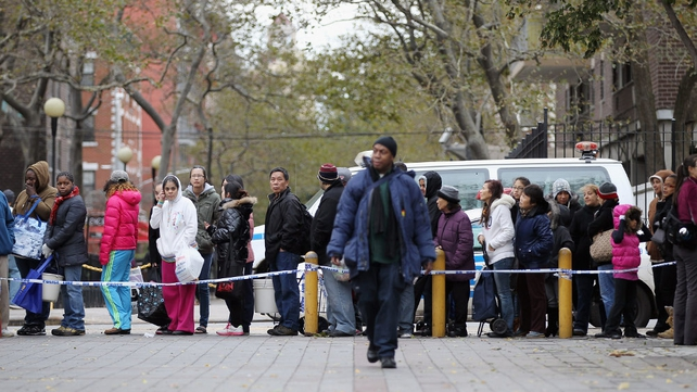 People stand outside a distribution center for basic supplies like nappies, food and water in NYC