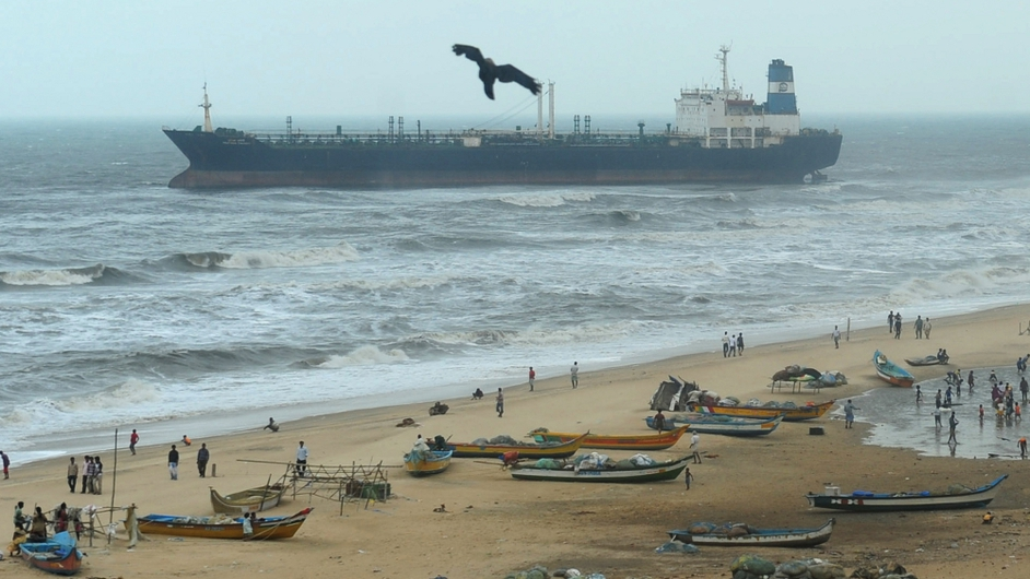 Indian fishing boats rest on a beach near the oil tanker ship Pratibha Cauvery after the ship ran aground 31 October off the coast in Chennai