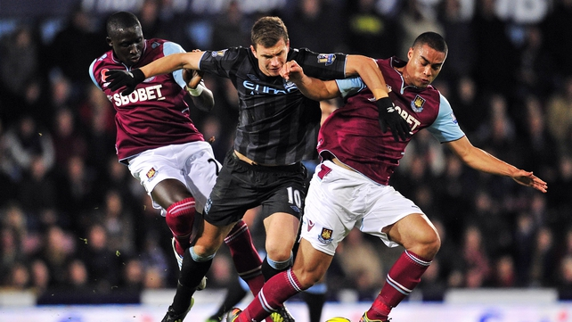 Manchester City striker Edin Dzeko is sandwiched between West Ham's Winston Reid (r) and Mohamed Diame