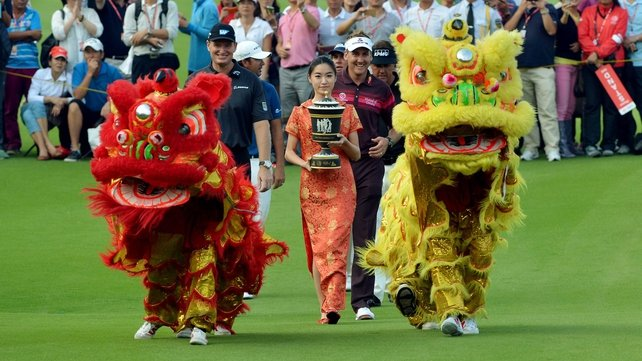 Ian Poulter is all smiles as he walks behind the HSBC trophy he won in China on Sunday