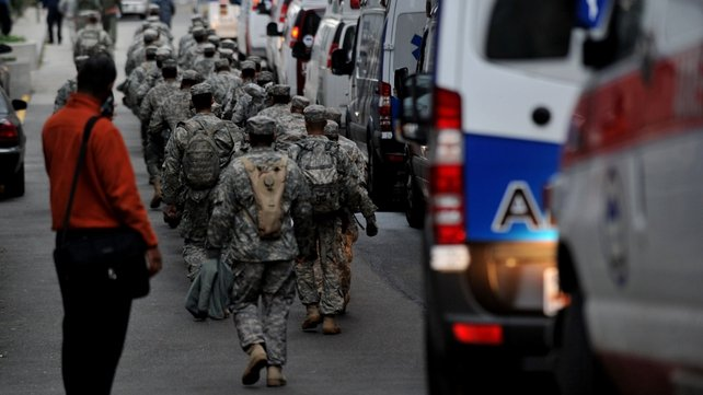 National Guard soldiers walk past ambulances at Bellevue Hospital during a planned evacuation