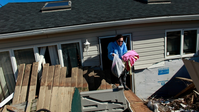 A woman sifts through her mother's damaged home in Queens