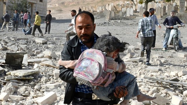 A Syrian man carries an injured girl following an air strike by government forces on the town of Al-Bab