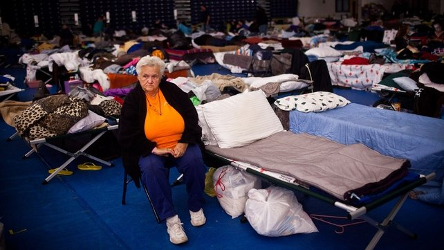 A woman sits next to her bed in a Red Cross evacuation shelter