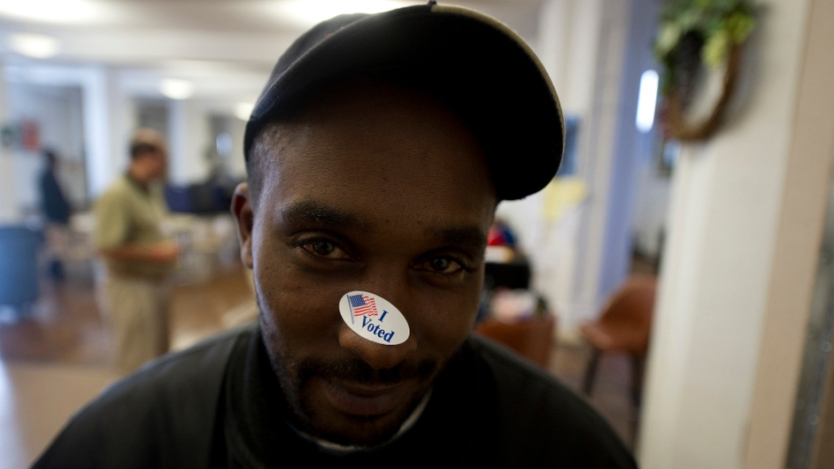 Brad Walker, 36, a first-time voter, puts his sticker on his nose after casting his ballot in Youngstown, Ohio.