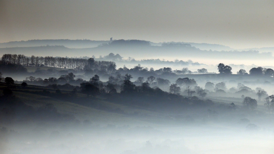 Mist lingers in fields viewed from Glastonbury Tor as the sun rises over the Somerset countryside