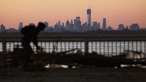 A man bikes past debris in the Rockaway neighbourhood with the Manhattan skyline in the background
