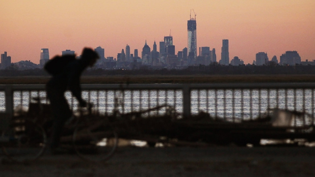 A man bikes past debris in the Rockaway neighbourhood with the Manhattan skyline in the background