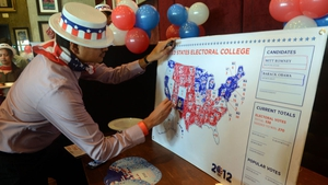 A US consulate staff member marks a US map in Republican and Democrat colours at an election party in Mumbai