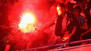 A fan lets off a flare during the Capital One Cup fourth round match between Chelsea and Manchester United at Stamford Bridge