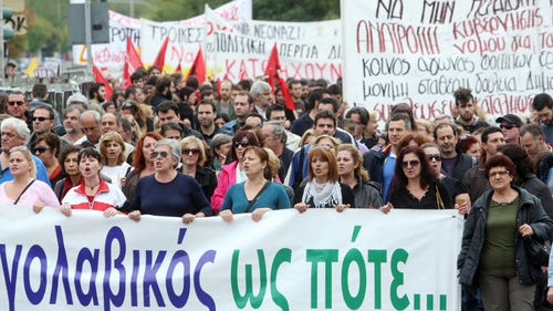 A sea of Greeks braved a steady downpour holding flags and banners standing before riot police guarding parliament.