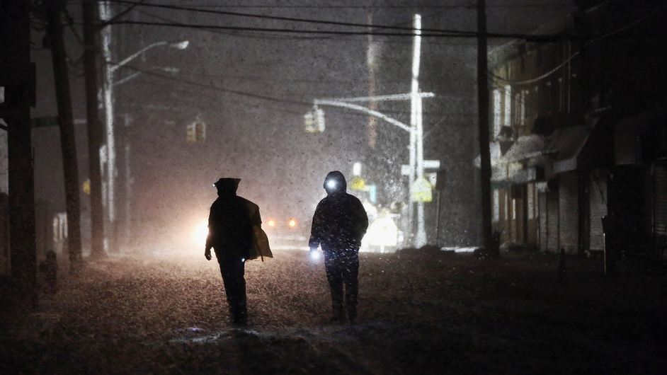 People walk through a darkened street using flashlights as a police spotlight shines behind them during a snowstorm in the Rockaway neighborhood of New York