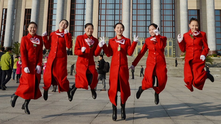 Chinese hostesses jump before the opening session of the Chinese Communist Party's five-yearly Congress at the Great Hall of the People in Beijing