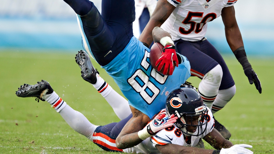 Chris Johnson No 28 of the Tennessee Titans is tackled and is tripped upside down against the Chicago Bears in Nashville, Tennessee