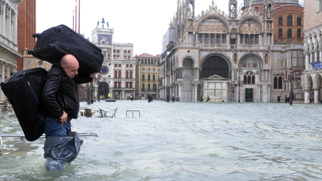 A man carries luggage across a flooded St Mark's square