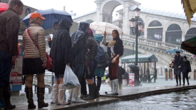 Tourists walk on footbridges near the Rialto bridge in Venice