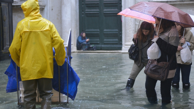 People walk in a flooded street during a 'acqua alta' in Venice