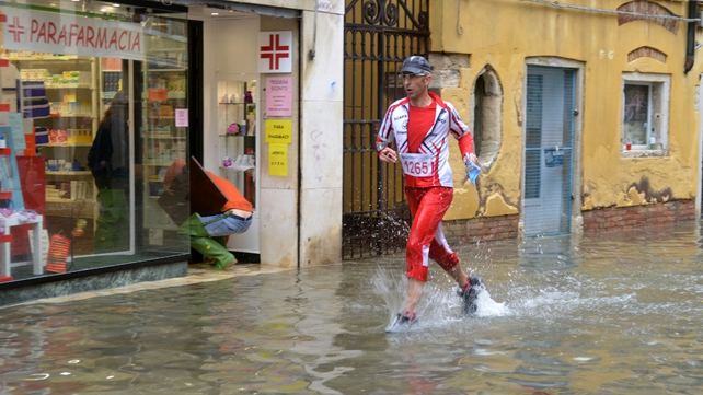 A man runs in a flooded street in Venice