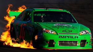 Danica Patrick drives her wrecked Chevrolet as flames shoot from the back after a crash at Phoenix International Raceway
