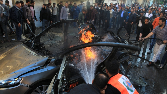 Palestinian firefighters extinguish fire from the car of Ahmaed Jaabari