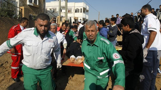 Palestinian rescue teams carry a wounded person following an Israeli air strike on Beit Lahia in the northern Gaza Strip