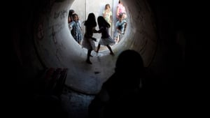 Israeli children play in a large concrete pipe used as a bomb shelter between rocket attacks from the Gaza Strip in Nitzan