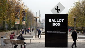 People pass a mock ballot box erected to encourage people to vote in the first Bristol mayoral election in England