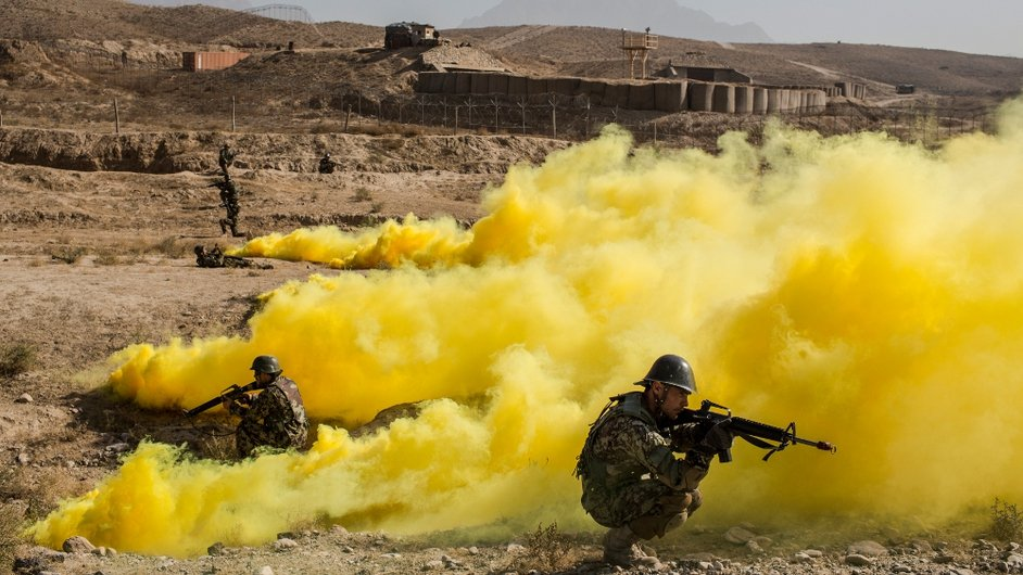Afghan National Army cadets secure the perimeter as smoke bombs, simulating detonated IEDs, cover the area during a Taliban capture military exercise at the Kabul Military Training Centre