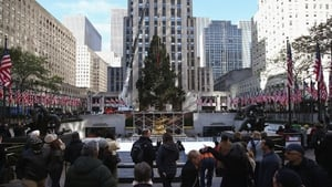 People watch as the Rockefeller Center Christmas tree is raised into position in New York City