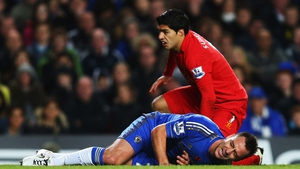 John Terry of Chelsea is injured in a collision with Luis Suarez of Liverpool during the English Premier League match between Chelsea and Liverpool at Stamford Bridge