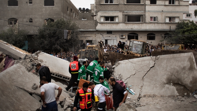 Palestinian firefighters and rescue personnel work at a blast site following an Israeli air raid in Gaza