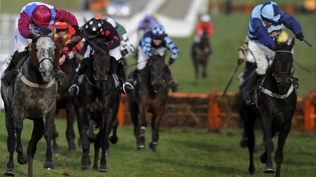 Paddy Brennan drives Olofi (left) to victory in the Racing Post Hurdle, with Cash And Go (right) third