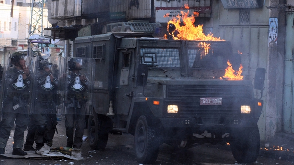 Israeli troops stand by an armoured vehicle that has been attacked by Palestinian protesters
