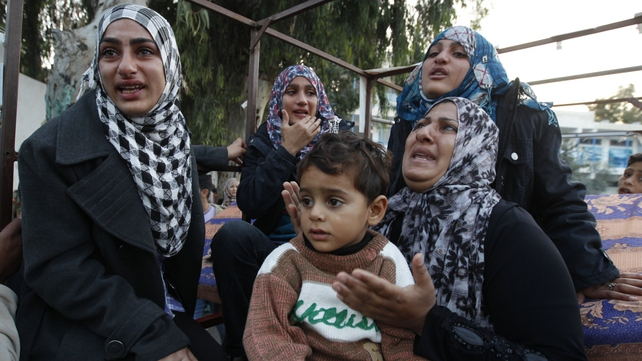 Palestinian women cry after they evacuated their homes to take shelter at a United Nations school in Gaza