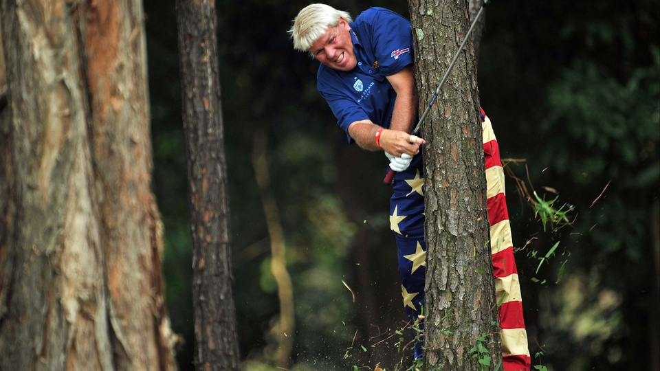 John Daly plays an awkward shot from the trees during the first round of the UBS Hong Kong open