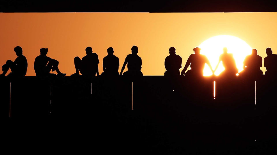 Oman fans watch while the sun sets during a World Cup Asian qualifier match between Oman and Japan