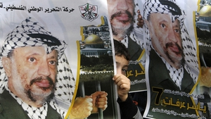 Palestinians hold up posters of former leader Yasser Arafat during ceremonies across the West Bank to mark the eighth anniversary of his death on 11 November 2012