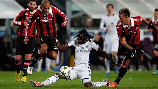 Dieudonne Mbokani of Anderlecht tackles Nigel De Jong of AC Milan