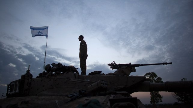 A soldier stands on his tank in a deployment area near Israel's border with Gaza