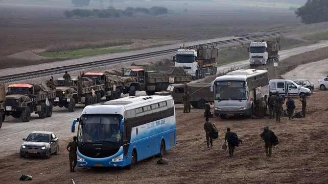 Israeli reserve soldiers and army vehicles depart the Gaza border area following Wednesday's truce
