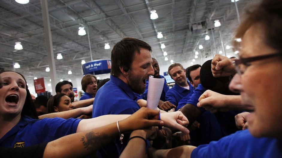 Best Buy employees in Naples, Florida, participate in a group huddle as they prepare to open the store on Thanksgiving Day, hours before the start of 'Black Friday'