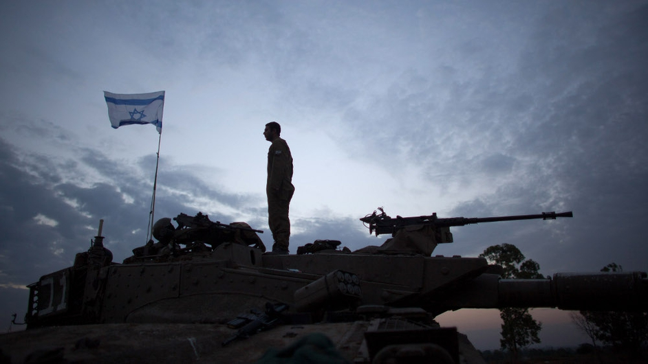 An Israeli soldier stands on his tank in a deployment area on Israel's border with the Gaza Strip