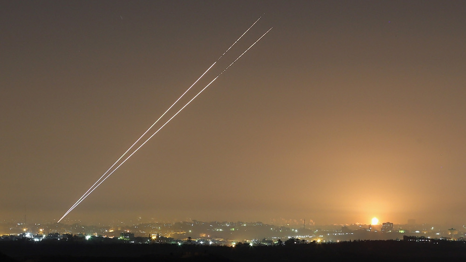 During the last hour of hostilities, militants launch rockets from Gaza City as an Israeli bomb explodes on the horizon