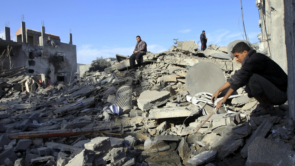 Palestinians look at their destroyed homes following Israeli air strikes on the southern Gaza Strip town of Rafah