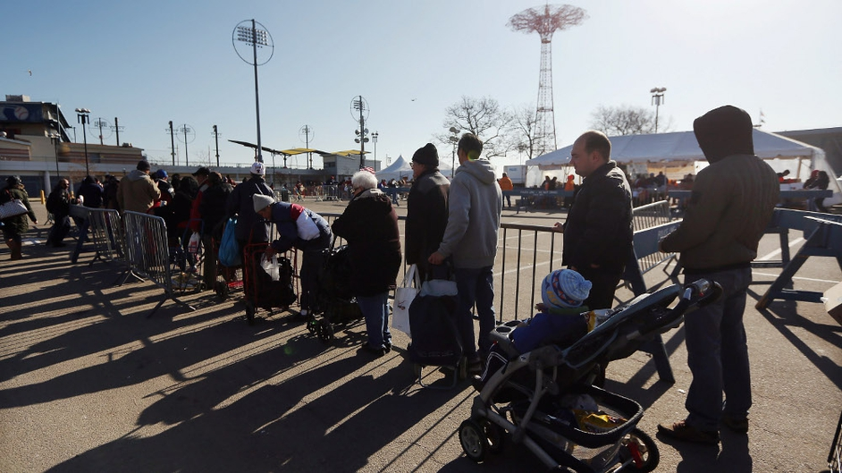 People wait in line to collect free food at a distribution point on Thanksgiving Day in the Coney Island neighbourhood of Brooklyn, New York