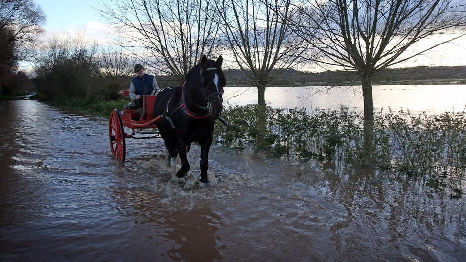 A horse and cart passes flooded fields and roads close to the village of North Curry near Taunton, England