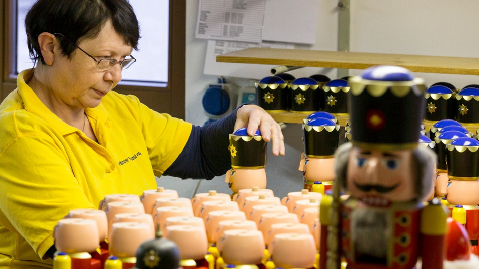 Artisan Martina Beyer, at the Seiffener Volkskunst Christmas decorations manufactory, assembles a nutcracker in Seiffen, Germany