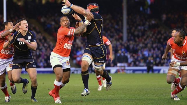 Alasdair Strokosch of Scotland tries to offload under pressure from Fetu'u Vainikolo of Tonga
